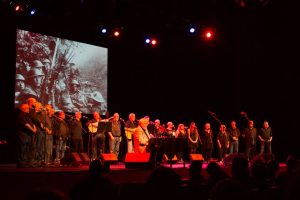 Photograph of the cast of Far, Far from Ypres onstage with projected graphic in the background